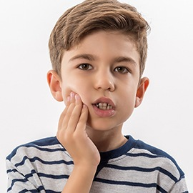 Boy in pain holding jaw