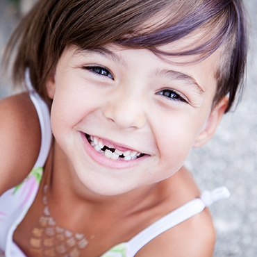 Smiling girl with missing front teeth