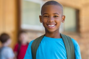 middle schooler smiling with backpack on