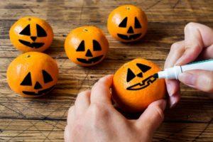 hand drawing jack-o-lantern faces on oranges
