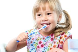 little girl with pigtails brushing her teeth