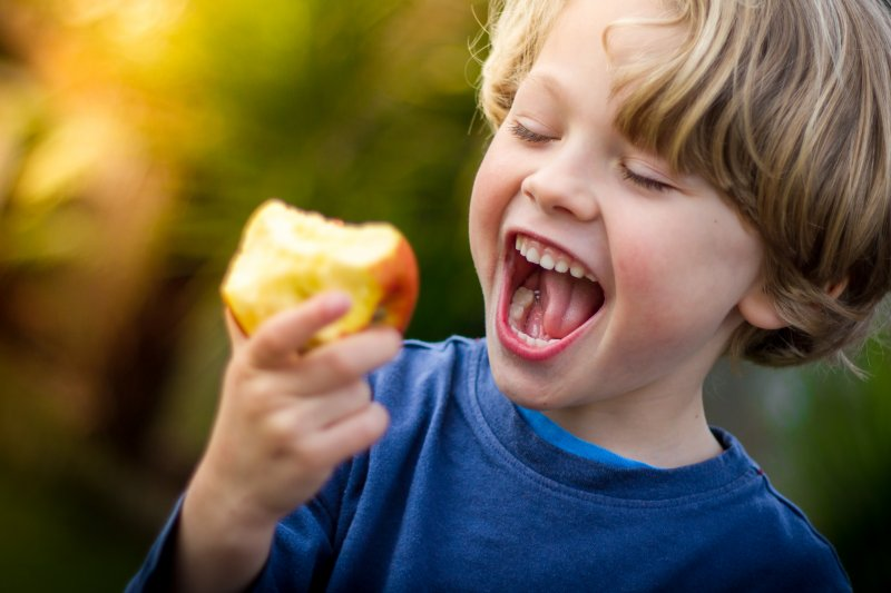 Child smiling while eating an apple